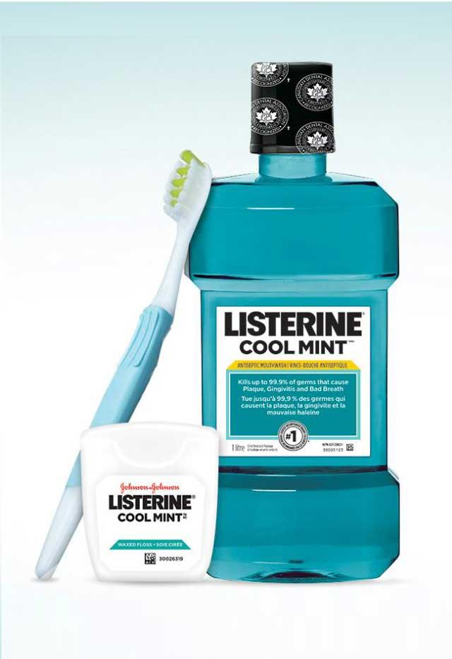 Listerine mouthwash bottle with floss and tooth brush beside it
